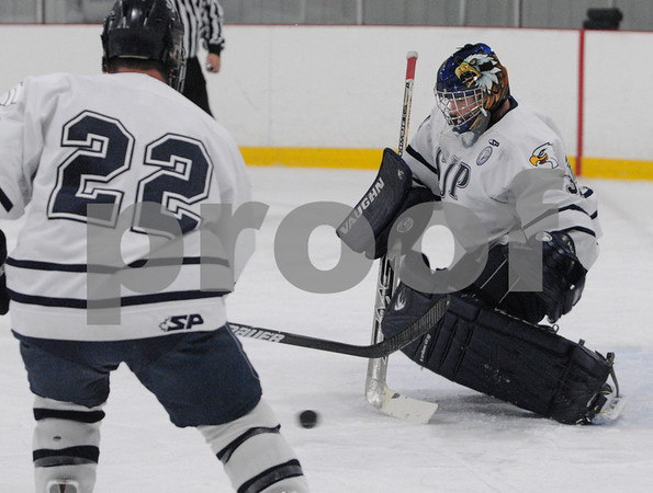 Wilmington:<br /> St. John's Prep goalie, Jonathan Siderewicz, goes for the puck in the game against Catholic Memorial at Ristuccia Arena.<br /> Photo by Ken Yuszkus/Salem News, Tuesday December 30, 2008.