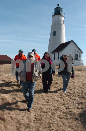 Salem:<br /> Robert Leavens, in front, who lives on the island, and from left in back of him, Luke Dlhopolsky and Al Spambler, both from the U.S. Coast Guard, Pamela Corcoran from Baker's Island Association, and Betsy Ware, care taker for the association, walk near the lighthouse on Baker's Island. The group toured the land at the lighthouse.<br /> Photo by Ken Yuszkus/Salem News, Wednesay, March 26, 2009.