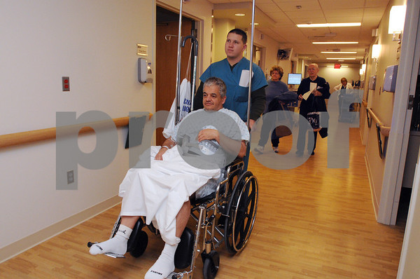 Salem:<br /> Patient John Spagnoli of Swampscott, is wheeled to his new private room, which was one of 32 private rooms that were being occupied as part of a $30-million renovation project at the North Shore Medical Center. Christopher Johansen, support associate, is wheeling him down the corridor to his new room.<br /> Photo by Ken Yuszkus/Salem News, Wednesday,  January 7, 2009.