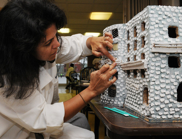 Danvers:<br /> Sabina Petersen adds transparent candy windows to a model of the Copley Plaza Hotel. NSCC culinary students are preparing a giant Copley Square for display in Boston.<br /> Photo by Ken Yuszkus/Salem News, Monday November 30, 2009.