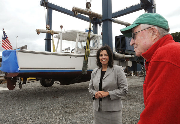 Salem:<br /> Thomas G. Brown, Jr., right, of Gloucester, donated his 34' Webber Cove power boat, in the background, valued at $45,000 to Sail Salem. Salem Mayor Kim Driscoll is on the left at Dion Yatch Yard.<br /> Photo by Ken Yuszkus/Salem News, Tuesday, August 16, 2011.