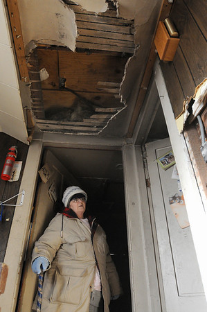Salem:<br /> Mary Ahearn looks toward the damage in her hallway ceiling which was the result of the fire in her home at 4 Buffum Street on December 18.<br /> Photo by Ken Yuszkus/Salem News, Wednesday, December 30, 2009.