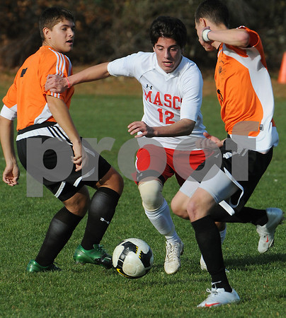 Topsfield:<br /> Marshall Wade of Masconomet, center, moves the ball down field between Woburn players during the Masconomet vs Woburn boys soccer Division 1 North state tournament at Masconomet High School.<br /> Photo by Ken Yuszkus/Salem News, Monday November 9, 2009.