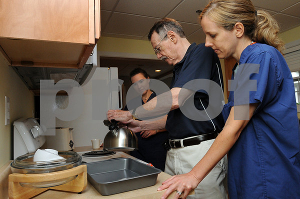 Swampscott:<br /> From left, Irina Shulman, language pathologist, Bill Culbert, and Megin Hemmerling, occupational therapist, work together as Bill makes coffee in a home setting at the Aviv Centers for Living Jewish Rehabilitation Center.<br /> Photo by Ken Yuszkus/Salem News, Thursday, July 16, 2009.
