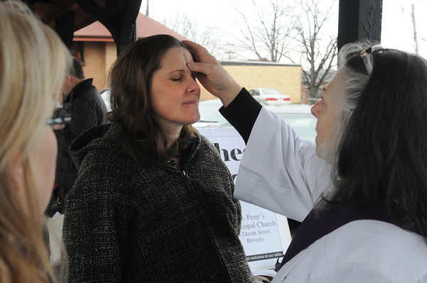 Beverly:<br /> Kathy Gratton of Beverly has ashes applied to her forehead by Gay Cox, deacon of St. Peter's Episcopal Church in Beverly, at the Beverly train depot early Ash Wednesday morning.<br /> Photo by Ken Yuszkus/Salem News, Wednesday,  February 22, 2012.