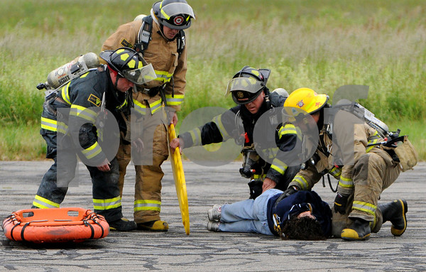 Beverly:<br /> Firefighters attend to one of the victims on the tarmack at the Beverly Airport during a simulated plane crash.<br /> Photo by Ken Yuszkus/Salem News, Thursday, June 11, 2009.