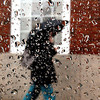 Beverly:<br /> A pedestrian with an umbrella walks in the wind driven rain on Cabot Street past a holiday wreath. The scene was photographed through a car window covered with water droplets.<br /> Photo by Ken Yuszkus/Salem News, Wednesday, Decmber 9, 2009.