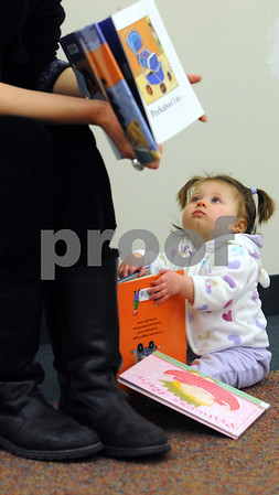 Hamilton:<br /> Isabelle Mae Westcott, 9 months old, plays with books while listening to Linda Cappabianca, childrens library assistant, read four storybooks during the storytime at the Hamilton-Wenham Public Library on Friday morning.<br /> Photo by Ken Yuszkus/Salem News, Friday December 19, 2008.