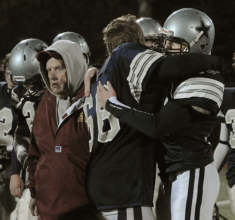 Reading:<br /> Hamilton-Wenham's Domenick Vogus, left, and Matt Vogus hug at the conclusion of the Hamilton-Wenham vs Cardinal Spellman state football playoff semi-final Division 3A game at Reading High School field where Hamilton-Wenham lost.<br /> Photo by Ken Yuszkus/Salem News, Tuesday November 30, 2010.