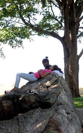 Salem:<br /> Gilda Borbon and in back of her is Tarra Brice, rest on a large rock in the shade during the middle of the day at Salem Willows.<br /> Photo by Ken Yuszkus/Salem News, Monday, August 1, 2011.
