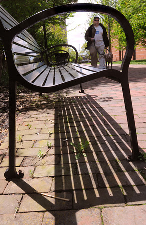 Salem:<br /> John Adelman of Salem, with his dog, Sarah, are framed by a metal bench while walking along the sidewalk near the Peabody Essex Museum.<br /> Photo by Ken Yuszkus/Salem News, Friday, May 11, 2012.
