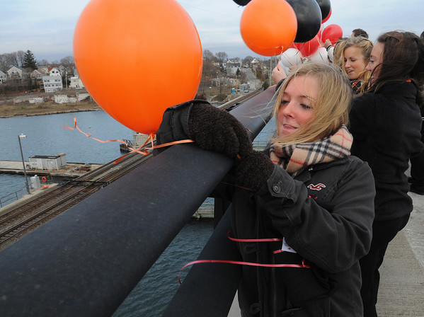 "Salem/Beverly:<br /> Stephanie Pierce, Beverly cheerleader, ties a balloon on the railing in the middle of the Veterans Memorial bridge at the start of the ""Bridging the Gap"" ceremony. Both Beverly and Salem tied balloons on the bridge.<br /> Photo by Ken Yuszkus/Salem News,  Monday,  November 22, 2010."