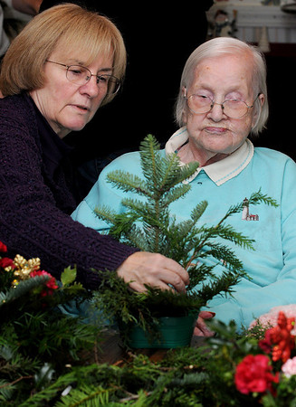 Beverly:<br /> Ellen Todd of Beverly, left,  a Friendly Garden Club member, helps Betty Cahill, a resident at the Ledgewood Rehabilitation and Skilled Nursing Center, make a holiday decoration. The garden club presented the holiday decorating class at the healthcare facility and the members assisted the residents as they created their decorations.<br /> Photo by Ken Yuszkus/Salem News, Friday, December 18, 2009.