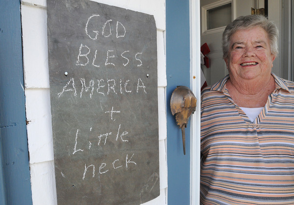 """Ipswich:<br /> Mary Varney, a longtime resident of Little Neck, stands in her front doorway near her chalk board with a message which reads """"God bless America + Little Neck"""". It was in response to last week's sale of the peninsula to the residents by the Feoffees, the trustees of the land that had been owned by the trust for 351 years until last Friday's sale.<br /> Photo by Ken Yuszkus/The Salem News, Friday, August 17, 2012."""