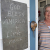 "Ipswich:<br /> Mary Varney, a longtime resident of Little Neck, stands in her front doorway near her chalk board with a message which reads ""God bless America + Little Neck"". It was in response to last week's sale of the peninsula to the residents by the Feoffees, the trustees of the land that had been owned by the trust for 351 years until last Friday's sale.<br /> Photo by Ken Yuszkus/The Salem News, Friday, August 17, 2012."