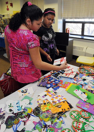 Salem:<br /> Aisha Pena, left, and Jadeliz Flores, both fourth graders at the Horace Mann Lab School, look over some of the items made by the Horace Mann Lab School students that were for sale at the Harvest Fair at the school.<br /> Photo by Ken Yuszkus/Salem News,  Thursday,  November 18, 2010.