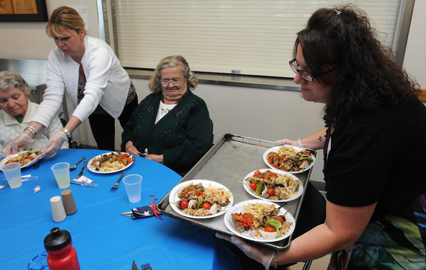 Danvers:<br /> From left, Rocasse Masse is served by Meredith Anderson as Eleanor Kudera waits to be served and Jennifer Tineo places her tray of food down at the Danvers Family Festival Senior Citizen Lunch held at the Danvers Senior Center.<br /> Photo by Ken Yuszkus/Salem News, Tuesday, June 26, 2012.