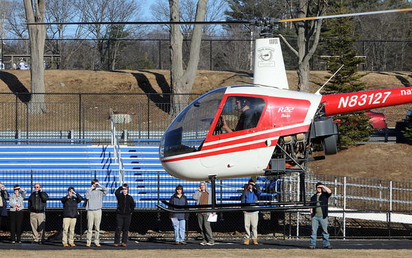 Danvers:<br /> St. John's Prep, senior Erik Slettehaugh of Groveland, pilots a helicopter over the Cronin Stadium field at St. John's Prep school as he takes off. He had landed in the stadium. Chris Ramsey, flight instructor, is seen in the window.<br /> Photo by Ken Yuszkus/Salem News, March 10, 2010.