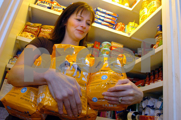 Boxford:<br /> Kathy Spencer holds bags of dogfood, which was one of her latest bargains, in front of her well stocked shelves in her pantry closet. Kathy Spencer started an online group to teach people how to shop for free. Now there are over 1,000 members.<br /> Photo by Ken Yuszkus/Salem News, Wednesday, April 1, 2009.
