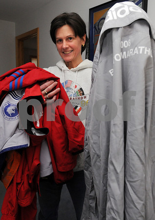 Hamilton:<br /> Mary Stephens has volunteered at one of the Boston Marathon water stops for 12 years with the local running club, the North Shore Striders. She's run marathons before. She is holding several jackets she received as a volunteer through the years. In her left hand is last year's jacket.<br /> Photo by Ken Yuszkus/Salem News, Thursday, April 16, 2009.