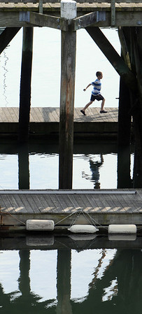 A boy runs along the dock at the Beverly wharf on Wednesday morning. Photo by Ken Yuszkus/Salem News.