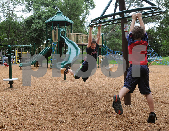 Salem:<br /> Cole Lamoureaux, left, and Calder Gebhardt swing on the new playground equipment at Forest River Park.<br /> Photo by Ken Yuszkus/Salem News, Wednesday, August 12, 2009.