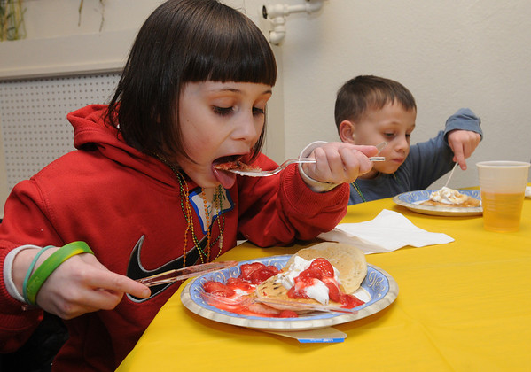 Danvers:<br /> Isabel Donahoe, 8, left, and her brother Timony Donahoe, 6, both of Danvers, enjoy their pancakes at the Shrove Tuesday Pancake Dinner at the Maple Street Church Tuesday evening in Danvers.<br /> Photo by Ken Yuszkus/Salem News, Tuesday March 8, 2011.