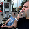 "Danvers:<br /> Maurizio Cotti, left, and Hector Duni, smoke cigarettes in front of the Cigars ""R"" Us storefront on Maple Street .<br /> Photo by Ken Yuszkus/Salem News, Wednesday, June 17, 2009."