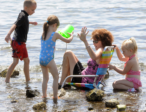 Beverly:<br /> From left, Chance Bonfanti, Emma Brown, Debbie Zakas, and Haley Booth stay cool at the edge of the water at Dane Street Beach. Debbie Zakas is the children's daycare provider.<br /> Photo by Ken Yuszkus/The Salem News, Wednesday, August 8,  2012.