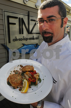 Salem:<br /> Dave Gillis, general manager of Finz Seafood and Grill, with Finz's signature crab cake dish.<br /> Photo by Ken Yuszkus/Salem News, Monday September 15, 2008.