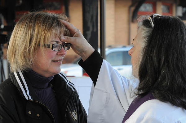 Beverly:<br /> Carrie Kimball Monahan of Beverly has ashes applied to her forehead by Gay Cox, deacon of St. Peter's Episcopal Church in Beverly, at the Beverly train depot early Ash Wednesday morning.<br /> Photo by Ken Yuszkus/Salem News, Wednesday,  February 22, 2012.