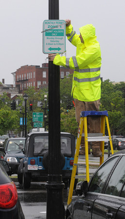 Salem:<br /> Mike Corsetti places new signs on a light pole in Riley Plaza during the rain.<br /> Photo by Ken Yuszkus/Salem News, Monday, June 25, 2012.