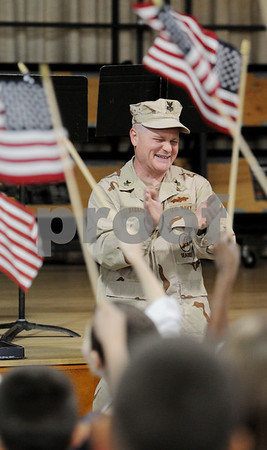 Peabody:<br /> Dan Barrasso, navy petty officer 1st class, reacts to the songs and flag waving of the first and third grades who were assembled at the McCarthy Memorial School for his presentation of a flag that flew over Iraq to the school. Dan just returned from Iraq.<br /> Photo by Ken Yuszkus/Salem News, Thursday April 4, 2009.