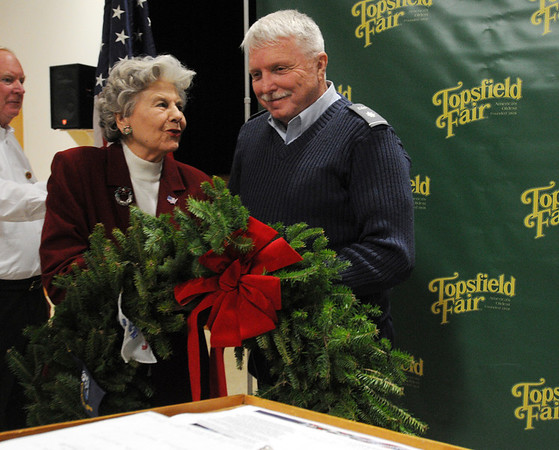 Topsfield:<br /> Joanne Patton accepts a wreath from Wayne Merritt, of the Wreaths Across America, during a ceremony in Coolidge Hall at the Topsfield Fair grounds. The  Wreaths Across America procession stopped to deliver wreaths and have lunch before heading for Arlington National Cemetery.<br /> Photo by Ken Yuszkus/Salem News, Monday, December 5, 2011.