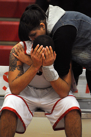 Salem:<br /> Salem's Antonio Reyes is consoled by his cousin, Sarai Pena, just after Lynn English beat Salem High School during the boys basketball title for the Northeastern Conference title.<br /> Photo by Ken Yuszkus/Salem News, Tuesday, February 15, 2011.