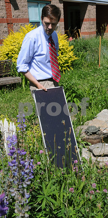 Salem:<br /> Kevin Andrews, Bentley Elementary teacher, holds the solar panel that powers a small fountain located in the school courtyard pond. Kevin Andrews, purchased the supplies to build the fountain with a Foundation for Salem Public Education grant. The students at the school help build the fountain.<br /> Photo by Ken Yuszkus/Salem News, Wednesday, June 17, 2009.
