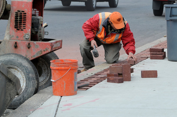 Salem:<br /> Francisco Carreiro placing blocks along the sidewalks on Bridge Street. Andre Benjamin, not pictured, was cutting the blocks.<br /> Photo by Ken Yuszkus/Salem News, Tuesday, April 10, 2012.