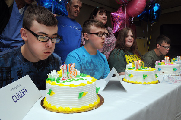 Beverly:<br /> Quadruplets from left, Cullen, Killian, Emma, and Riley Driscoll blow out the candles on their birthday cakes at their 15th birthday party held at Beverly Hospital. Their parents David and Mary Driscoll are standing in back. <br /> Photo by Ken Yuszkus/Salem News, Friday, July 13,  2012.