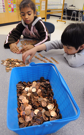 Salem:<br /> Stephanie Aguiar dos Santos, left, and Lam Ngo count out a hundred pennies to add to the total for the Pennies for Peace. The first and second graders at the Bates School will give the final amount to Greg Mortenson when he comes to Salem on May 1 to accept the Salem Award.<br /> Photo by Ken Yuszkus/Salem News, Friday, April 16, 2010.
