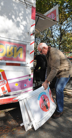 Salem:<br /> John Flynn, owner of Fiesta Shows Foods, loads signs for the popcorn cotton candy trailer, which he is standing next to, as he prepares the trailer to leave the Salem Common. Now that Halloween is over, Salem is changing back to normal.<br /> Photo by Ken Yuszkus/Salem News, Tuesday, November 31, 2011.