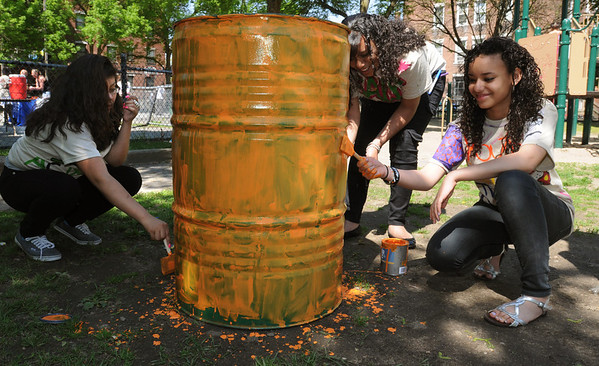 "Salem:<br /> From left, Kimberly Ramirez, Tahisha Reynoso, and Sabrina Ortega, all 7th graders at the Salem Academy Charter School, paint one of the trash cans at Mary Jane Lee Park. Painting the trash cans is the first part of creating their ""Trashketball"" project.<br /> Photo by Ken Yuszkus/Salem News, Wednesday, May 25, 2011."