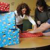 Danvers:<br /> From left, Jen Machado, Carla King, and Henry Witham, volunteers, wrap presents for a large holiday party for foster kids on Saturday evening.<br /> Photo by Ken Yuszkus/Salem News, Thursday, December 8, 2011.