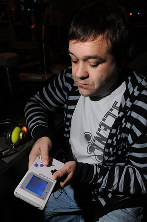 """Salem:<br /> Scott Buchanan, a dj and """"chip tune"""" musician, who uses hand-held gameboys and video game systems to make music. He is holding a gameboy.<br />  Photo by Ken Yuszkus/Salem News, Monday November 30, 2009."""