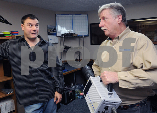 """Salem:<br /> Matt Kearney, left, host of """"Time Warp"""" on Discovery, speaks with Gene O'Connell, owner of Tech-Imaging Services. Gene is holding a Photron SA1 high speed camera which can shoot up to 675,000 frames per second.<br /> Photo by Ken Yuszkus/Salem News, Tuesday,  January 13, 2009."""