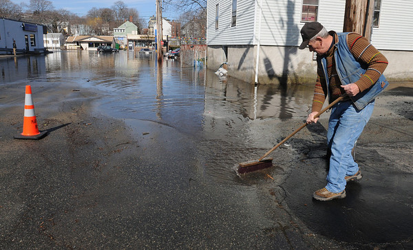 Peabody:<br /> Johnny DeRocha directs the water with a broom while sweeping up the area of Spring Street at Spring Street Court.<br /> Photo by Ken Yuszkus/Salem News, Tuesday, March 16, 2010.