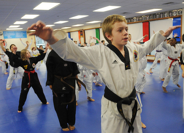 Beverly:<br /> Oscar Hawkes does jumping jacks during warm up  during practice of the childrens all belt class at DW Kim US Tae Kwon Do studio on Friday.<br /> Photo by Ken Yuszkus/Salem News, Friday, December 2, 2011.