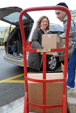 Peabody:<br /> Kim Marino brought boxes of dictionaries to the Brown School. Mannuel Melo, the school custodian, helps load the boxes onto a hand cart. The dictionaries were donated to the 4th graders by the Verizon Pioneers.<br /> Photo by Ken Yuszkus/Salem News, Tuesday, December 15, 2009.