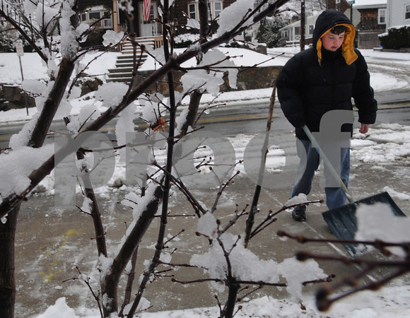 Beverly:<br /> The wet snow sticks to the branches of shrubs as Daniel Van Dyke, 12, shovels the snow from the walkway in front of his house and the driveway. The early morning snowfall turned into a sloppy mess. <br /> Photo by Ken Yuszkus/Salem News, Monday March 9, 2009.
