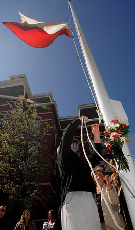 Peabody:<br /> Edward Nizwantowski, president of the St. Michaels Polish Society, lowers the flag to half staff in front of Peabody City Hall, as Lola Busta, president of the United Polish Organization, watches.<br /> Photo by Ken Yuszkus/Salem News, Monday, April 12, 2010.