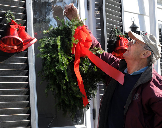 Beverly:<br /> George Zarkades hangs holiday decorations on the front of Phyllis Clark's house on a sunny but cool day.<br /> Photo by Ken Yuszkus/Salem News, Thurssday, Decmber 10, 2009.